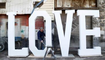 a-man-paints-letters-that-create-the-word-love-for-valentines-day-in-damascus.jpg